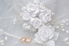 Vigselringar på brud- skyler med den vita boutonnieren på grå färger Royaltyfri Foto