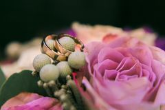 Vigselringar på brudbukett av rosor Närbildmakroskott arkivfoton