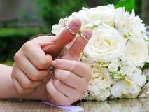 Vigselringar på deras fingerfolkmarrieds brud och brudgummen, målade roliga små män Royaltyfria Bilder