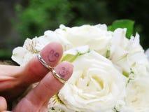 Vigselringar på deras fingerfolkmarrieds brud och brudgummen, målade roliga små män Royaltyfri Bild