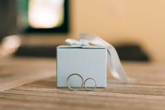 Vigselringar på en ljus trätextur i en blå ask Bröllop j Royaltyfri Foto