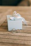 Vigselringar på en ljus trätextur i en blå ask Bröllop j Arkivbild