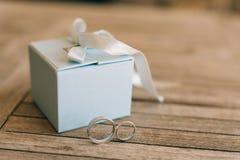 Vigselringar på en ljus trätextur i en blå ask Bröllop j Arkivfoto