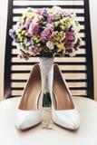 Vigselringar på en stol med skor för brud` s och en brud- bukett Royaltyfria Bilder