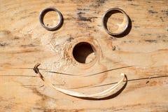 Vigselringar på ett träbräde som bildar en smiley, vänder mot Arkivfoton