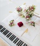 Vigselringar på ett vitt piano royaltyfria foton