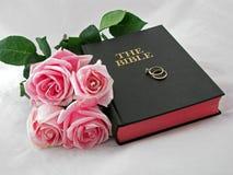 Vigselringar på helig bibel Arkivfoton