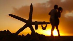 Vigselringar på sjöstjärnan och paren som kysser på solnedgångstranden, älskar begrepp arkivfilmer
