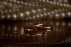 Vigselringar på tabellen med reflexion och halsbandet royaltyfri foto
