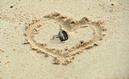 Vigselringar som lägger i sand i hjärtaform Fotografering för Bildbyråer