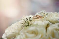 Vigselringar som ligger på bukett för vita blommor Royaltyfri Bild