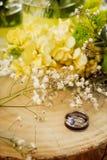 Vigselringstilleben på trä med blommor Royaltyfri Fotografi