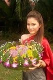 Vigueta bastante tailandesa de la flor del asimiento de la mujer. fotos de archivo libres de regalías