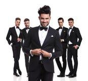 Vijf aantrekkelijke elegante mensen die zich met leider bevinden die zijn s dichtknopen royalty-vrije stock foto