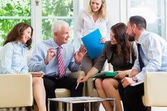 Vijf bedrijfsmensen in teamvergadering die grafieken bestuderen royalty-vrije stock foto's