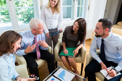 Vijf bedrijfsmensen in teamvergadering die grafieken bestuderen stock afbeelding