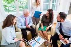 Vijf bedrijfsmensen in teamvergadering die grafieken bestuderen stock foto