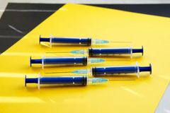 Vijf blauwe spuiten op een gele en zwarte oppervlakte in zon` s Ra stock afbeeldingen