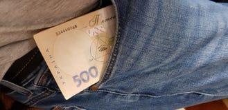 Vijf die honderd hryvniarekening in een jeanszak wordt gestapeld stock afbeelding