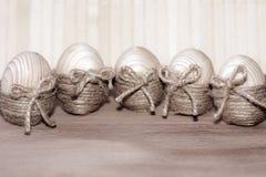Vijf die paaseieren in streng in de vorm van een nest op een houten achtergrond worden verpakt stock fotografie