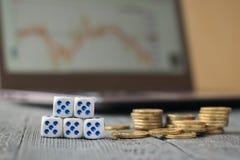 Vijf dobbelen en een stapel van muntstukken voor laptop met bedrijfsprogramma's Stock Afbeelding