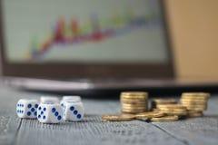 Vijf dobbelen en een stapel van muntstukken voor laptop met bedrijfsprogramma's op een donkere lijst Stock Foto