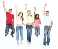 Vijf en vrienden die springen glimlachen Stock Fotografie