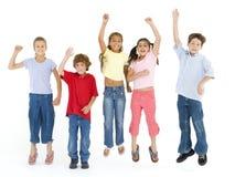 Vijf en vrienden die springen glimlachen Royalty-vrije Stock Afbeelding
