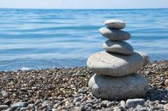Vijf evenwichtige stenen op een strand Stock Afbeelding