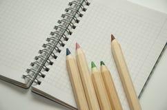 Vijf gekleurde houten potloden op de achtergrond van een leeg blad van blocnote stock afbeelding