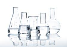 Vijf glasflessen met een duidelijke vloeistof Stock Foto's