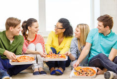 Vijf glimlachende tieners die pizza thuis eten Royalty-vrije Stock Foto