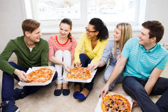 Vijf glimlachende tieners die pizza thuis eten Stock Fotografie