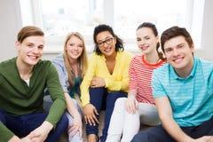 Vijf glimlachende tieners die pret hebben thuis Stock Foto's