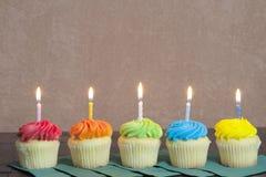 Vijf helder gekleurd cupcakes met aangestoken kaarsen Stock Foto's