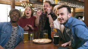 Vijf hipstervrienden die bier, cocktail drinken terwijl het toejuichen van voor sporten spel in bar, bar, stock footage