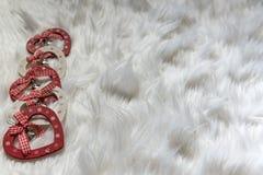 Vijf houten hart gevormde Kerstmisornamenten op witte pluizige stof, sluiten omhoog stock afbeelding