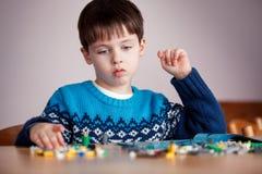 Vijf jaar het oude jongen spelen met bouwstenen Stock Afbeelding