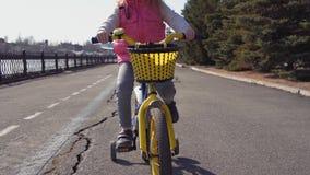 Vijf-jaar-oud weinig berijdende fiets van het blondemeisje in een oud park stock videobeelden
