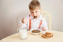 Vijf-jaar-oud in wit overhemd eet een kind linzen Royalty-vrije Stock Fotografie