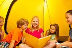 Vijf jonge geitjes gelezen boeken in een tent Stock Foto's