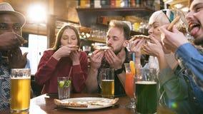 Vijf jonge hipstervrienden die pizza eten stock video