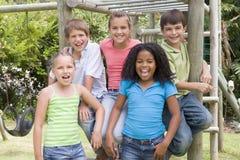 Vijf jonge vrienden bij speelplaats het glimlachen Stock Foto