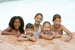 Vijf jonge vrienden in zwembad het glimlachen stock fotografie