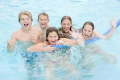 Vijf jonge vrienden in zwembad het spelen Royalty-vrije Stock Afbeeldingen
