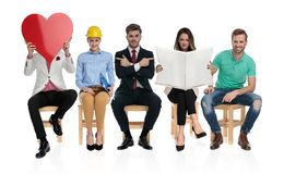 Vijf jongeren die pret hebben die op een baangesprek wachten stock fotografie