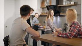 Vijf jongeren rust op kleine huispartij in vakanties, drinkt het paar wijn en zij vrienden koken stock videobeelden