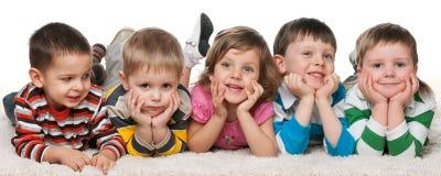 Vijf kinderen die op het tapijt liggen Stock Foto's