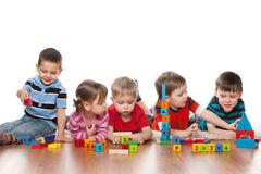 Vijf kinderen in kleuterschool stock foto's