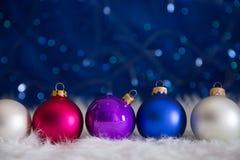 Vijf kleurrijke Kerstmisballen op wit bont met slingerlichten o Stock Fotografie